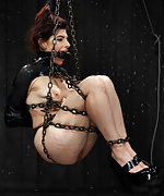 Latex woman gets cuffed, chained and dildoed